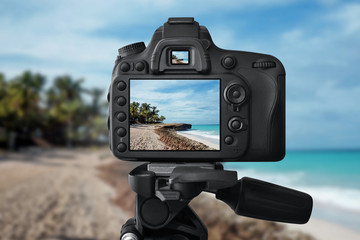 The camera on a tripod is taking a picture of the sea and beach