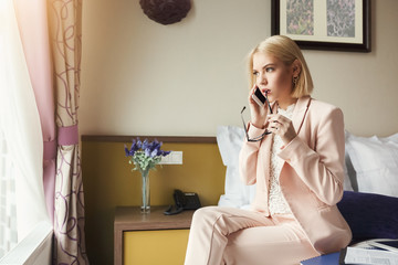 Serious woman talking on phone in hotel room