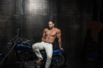 Young handsome sexy male fitness model poses on a gorgeous shiny motorcycle
