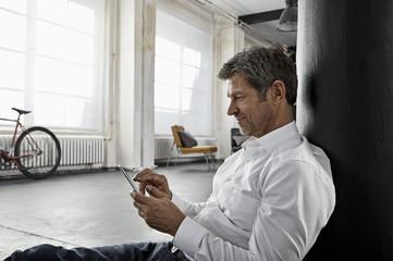 Portrait of mature business man using smartphone in loft