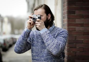 Mann fotografiert mit alter Kamera