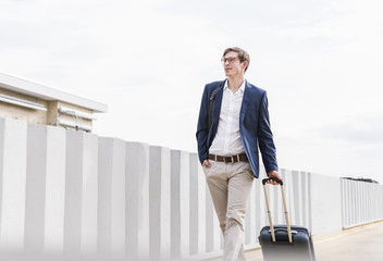 Confident businessman with rolling suitcase walking at parking garage