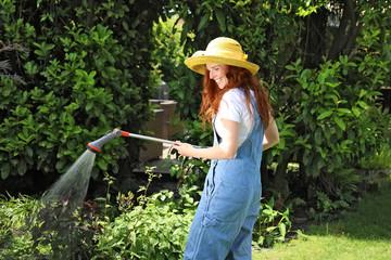 Hübsche rothaarige Frau bei der Gartenarbeit wässert mit einer Brause ein Beet