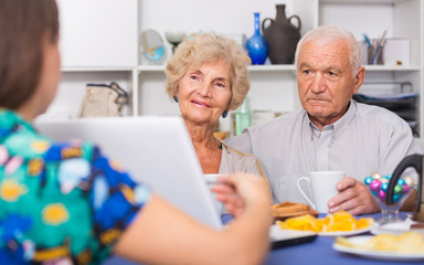 Young woman showing elderly couple something on laptop