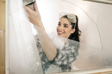 Young woman renovating her new flat, using cartridge dispenser