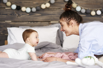 Mother and baby playing in bedroom