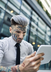 Young businessman with tattooed face, using digital tablet