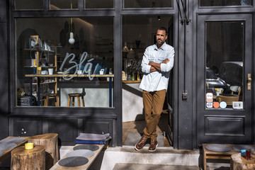 Man standing at entrance door of a cafe