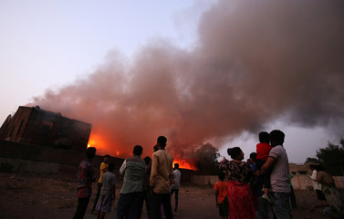 Onlookers watch a fire that broke out at a cotton processing unit in Ahmedabad