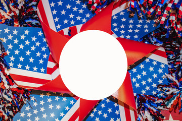 red whte and blue pinwheel with stars and strips  surrounded by tinsel with white circle for copy in center