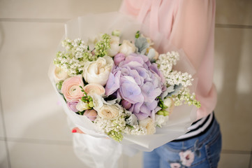 Girl holding a beautiful bouquet of violet tender flowers