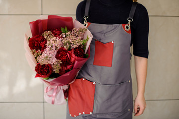 Girl holding a beautiful bouquet of red and rose colour flowers