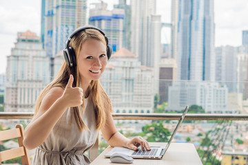 Young woman teaches a foreign language or learns a foreign language on the Internet on her balcony...
