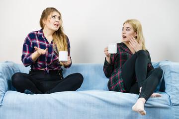 Female friends sitting on sofa talking