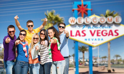 travel, tourism and people concept - group of happy friends pointing at you over welcome to fabulous las vegas sign background