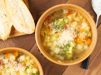 Two bowl of minestrone soup with toast on rustic wooden background, top view, close up
