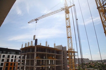 A modern new building. Working crane on the construction of the house. Construction site with cranes on sky background.