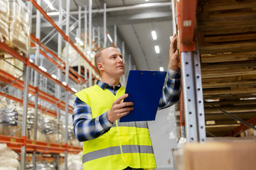 logistic business, shipment and people concept - male worker or supervisor with clipboard in reflective safety vest at warehouse