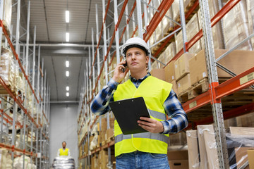 logistic business, technology and shipment concept - businessman calling on smartphone at warehouse