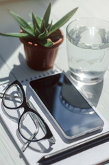 Close-up image of a smartphone, notebook with pencil, glass of water and pots with flowers at workplace.