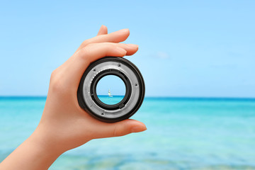 Hand holding camera lens on the beach, sea and sailing boat in the background. Travel and photography concept with empty space