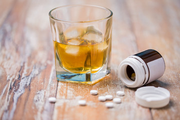 Foto auf AluDibond Bar drug abuse, addiction and suicide concept - glass of alcohol and pills on table