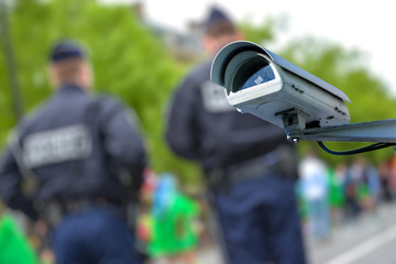 security CCTV camera or surveillance system with police officers on blurry background