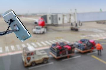 security CCTV camera or surveillance system with airport tarmac on blurry background