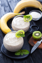 fresh banana smoothie with apple, kiwi and mint on a black wooden table.