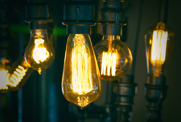 Vintage glowing light bulb lamp hanging. Interior decoration in old style luxury design. Focus on the foreground light.