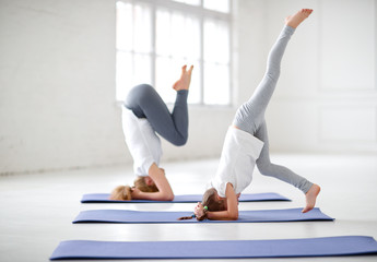 mother with child practicing yoga in headstand