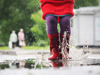 Child's feet in rubber boots. Summer, puddles, rain