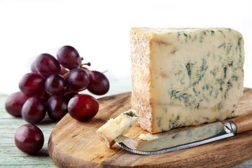 Stilton on a cheese board with red grapes and cheese knife