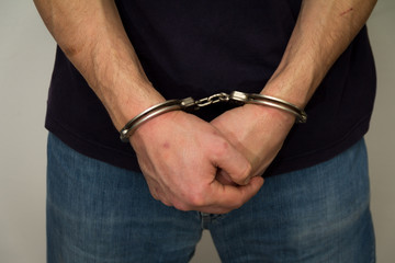 The criminal handcuffed. Hands with handcuffs in the front