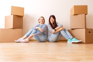Photo of two girls sitting on floor among cardboard boxes