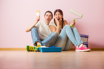 Photo of young woman and man with paint roller sitting on floor
