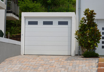 Moderne Beton-Garage mit Automatik-Tor an der gepflasterten Hofeinfahrt eines Wohnhauses