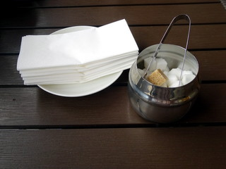 A stack of napkins on a saucer and a sugar bowl