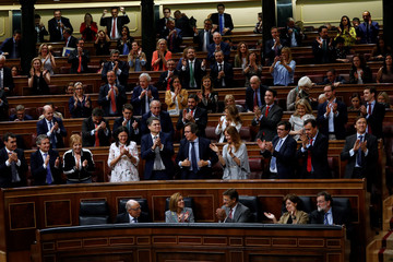 Spain's Treasury Minister Cristobal Montoro is applauded by fellow members of the Popular Party after voting to pass the 2018 budget at Spanish Parliament in Madrid