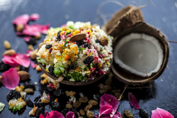 Close up of Indo and Islamic dessert dish Metha Zarda or Sweet Rice or Zarda or Shkrana with all dry fruit including coconut and sugar on wooden surface.