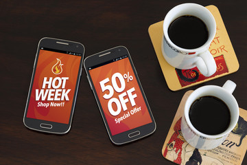 Hot Week 50% Off discounts. Advertising, Special Offer. Two cell phones and two coffee cup over the table. Marketing, Internet business. Sales.