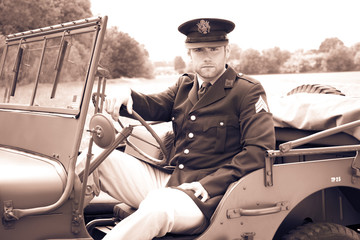 Handsome American WWII GI Army officer in uniform riding Willy Jeep
