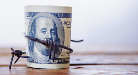 Fototapeta US Dollar money wrapped in barbed wire as symbol of economic warfare, sanctions and embargo busting obraz
