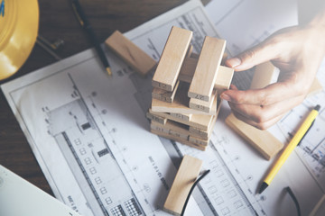 Man stacking wooden blocks. Development concept.
