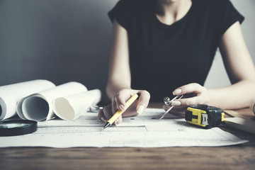 young woman architect working on blueprints spread out on a table