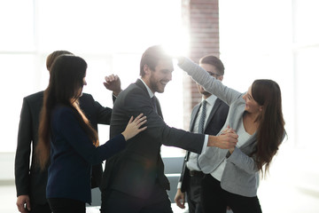 Portrait of an enthusiastic business team congratulating their c