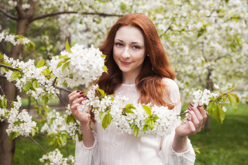 Young ginger hair woman near white tender blossoming tree. fairy dreamlike mood of the spring and summer. Beautiful romantic lady smiling bride, wedding. Copy space background.