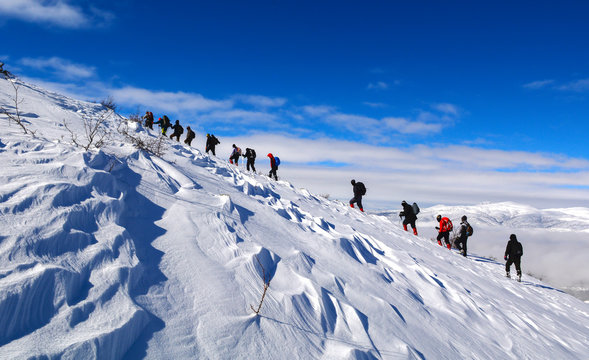 challenging winter walking event with crowded mountaineering group