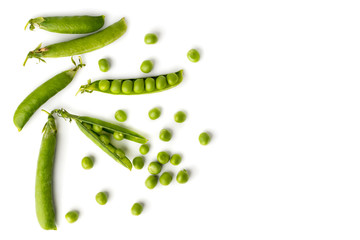 Green peas in pods and scattered on a white. The view from the top.