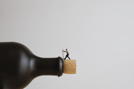 Closeup of a miniature worker opening a bottle